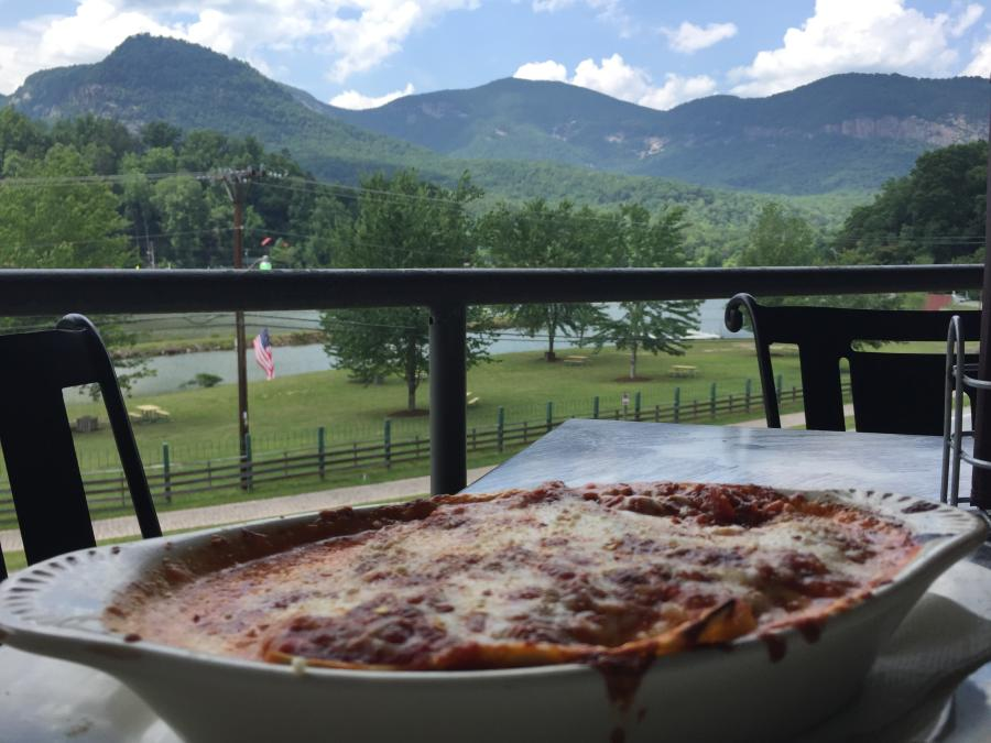 A view from the front patio of La Strada, showing food in the front and mountains.